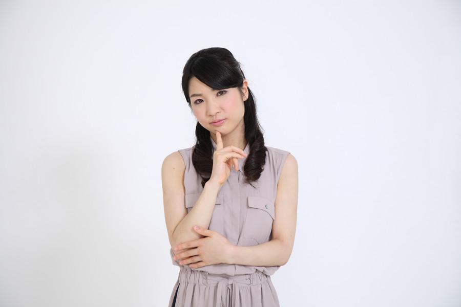 人差し指を顎に当て考えるポーズの女性