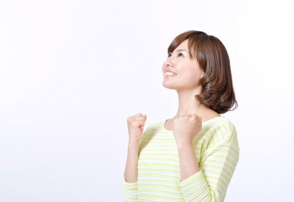 上を向いてガッツポーズをするポジティブな女性のイメージ